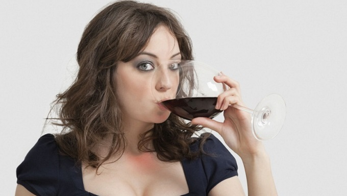 Portrait of beautiful young woman drinking wine against gray background